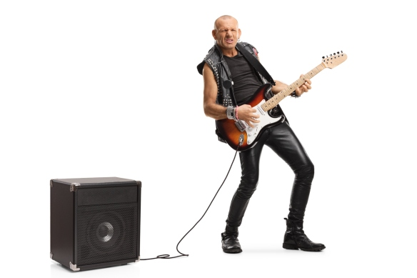 Bald musician playing a guitar plugged into an amplifier